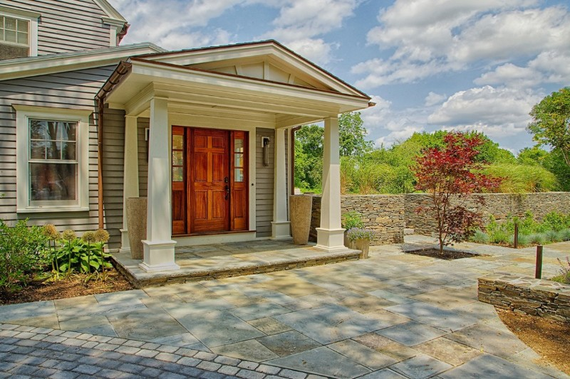 This large vestibule umbrellas over a bluestone entryway landing with a six-panel mahogany door, copper down spout, and flashing.
