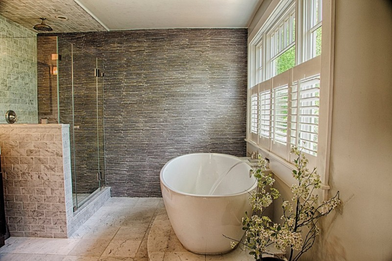 Spa tranquility with free standing soaking tub, floor to ceiling slate tiled wall, Carrera marble shower tile and flooring, and custom plantation shutters for privacy.