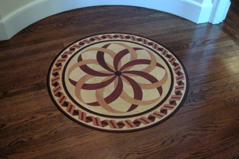 <strong>Medallion</strong><br>A medallion in-lay was installed in a stained, quarter-sawn, white oak flooring. The Estancia medallion contains American Cherry, Birdseye Maple, Merbau, and Wenge woods.