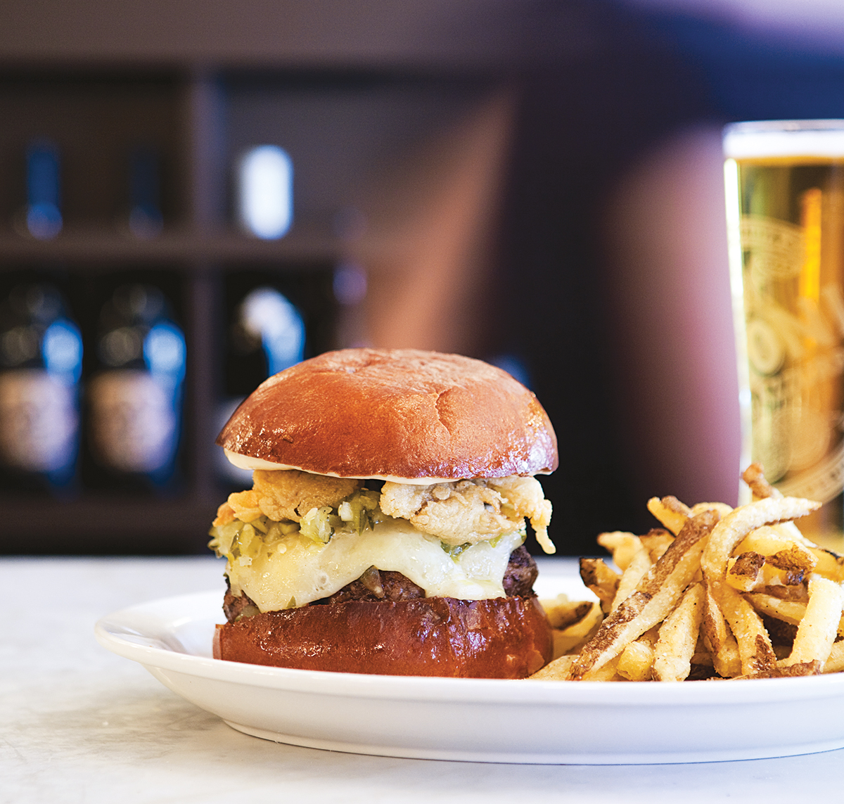 The neptuneburger comes laden with fried oysters and cheddar. Photo by Keller + Keller.