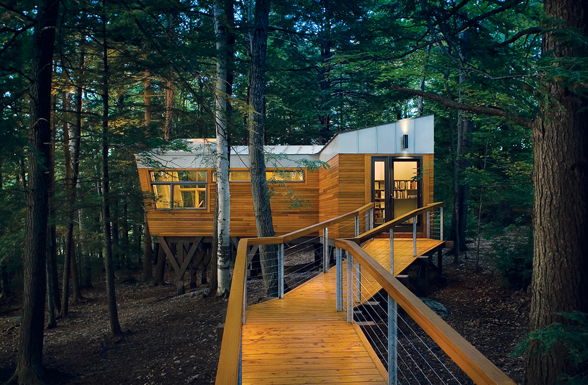 A long, winding boardwalk leads from the main house to the book-filled cabin in the forest.