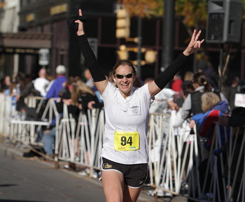 Gina crossing one of many finish lines. Photo provided.