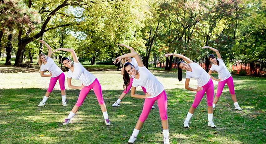 Working out in a park is fun! But we promise everyone won;t be in the same outfit. Group fitness photo via Shutterstock.