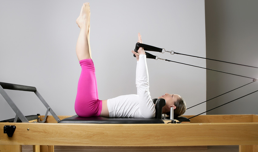 Woman doing reformer Pilates exercises. Photo via Shutterstock.