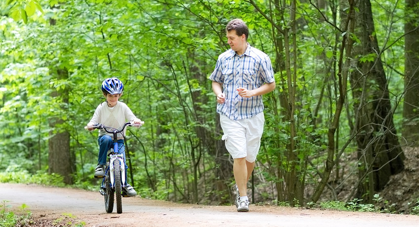 Teaching kids to wear bike helmets is important. Biking photo via Shutterstock.