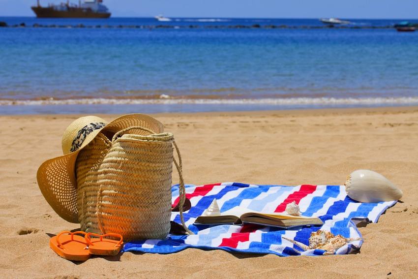 As temperatures head into the 90s, remember to bring a bottle of water to the beach to help yourself stay hydrated. Sunbathing image via Shutterstock.