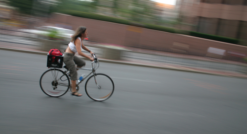 She should be in a bike lane. Cyclist in Boston image via Shutterstock.