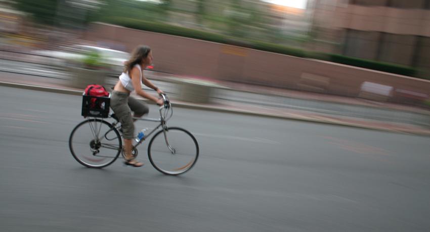 She should be in a bike lane. Cyclist in Boston image via Shutterstock.