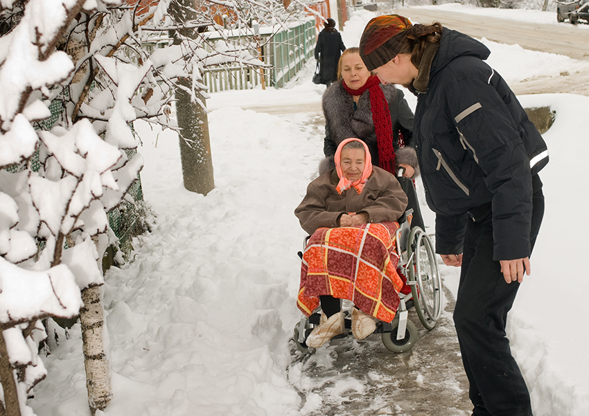 Clearing the snow for an elderly women photo via shutterstock