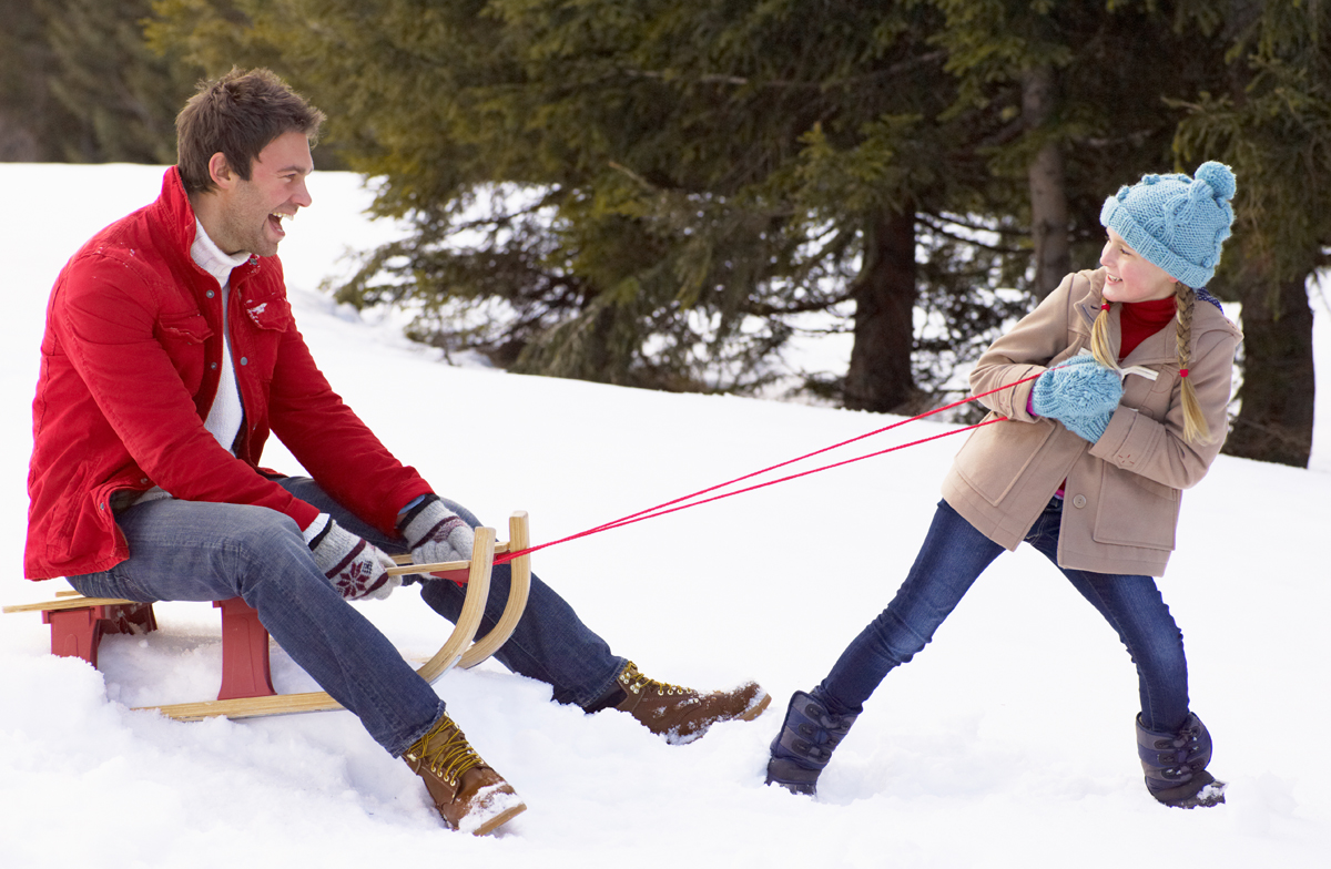 Girl pulling Dad on sled