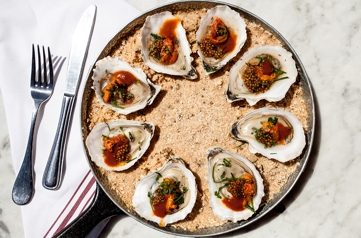 Roasted oysters served with fresh herbs, pickled mustard seeds, uni ...