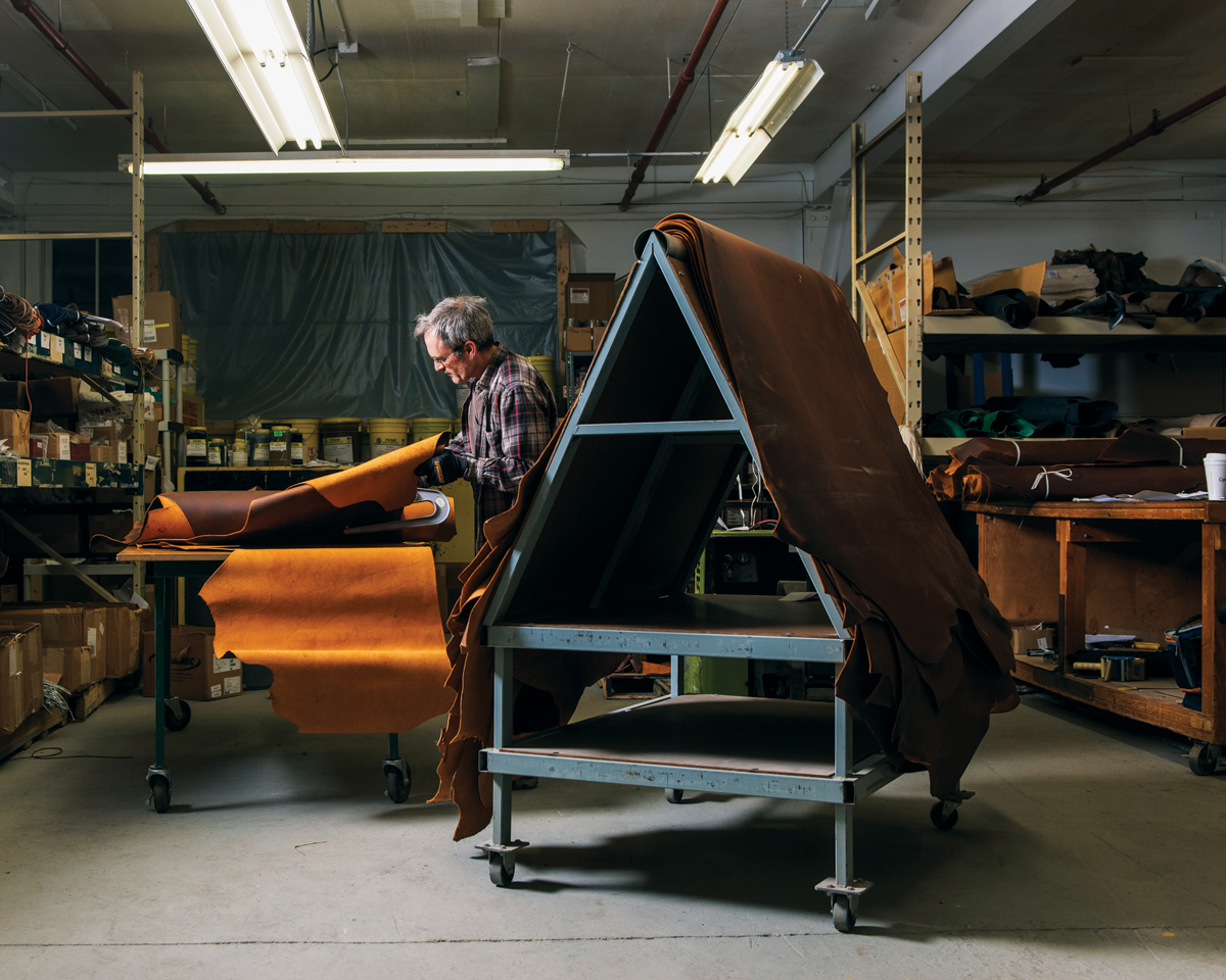 A craftsman sorts various leathers.