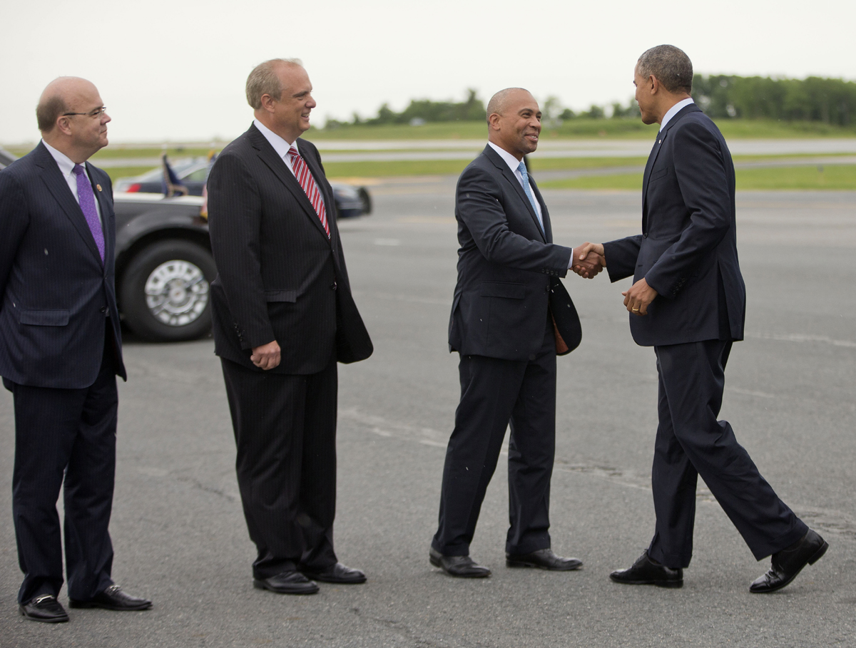 President Barack Obama is greeted by Gov. Deval Patrick, as Worcester Mayor Joseph Petty and Rep. Jim McGovern watch upon his arrival at Worcester Regional Airport. / AP Photo