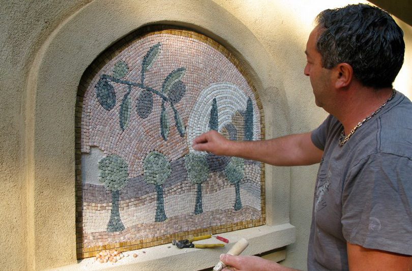 Mason Frank Corrado installs a mosaic by hand.