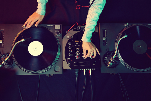 A DJ at the equipment deck via Shutterstock.