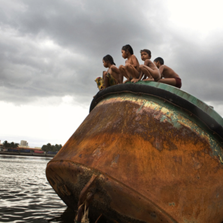 Enrique and his friends sit atop an old rusty tank and jump into the polluted Pasig river
