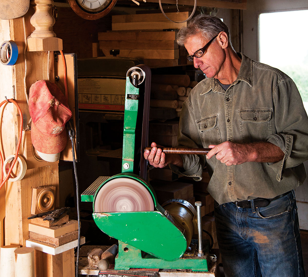 Ken works a piece of cherry on an electric sander.