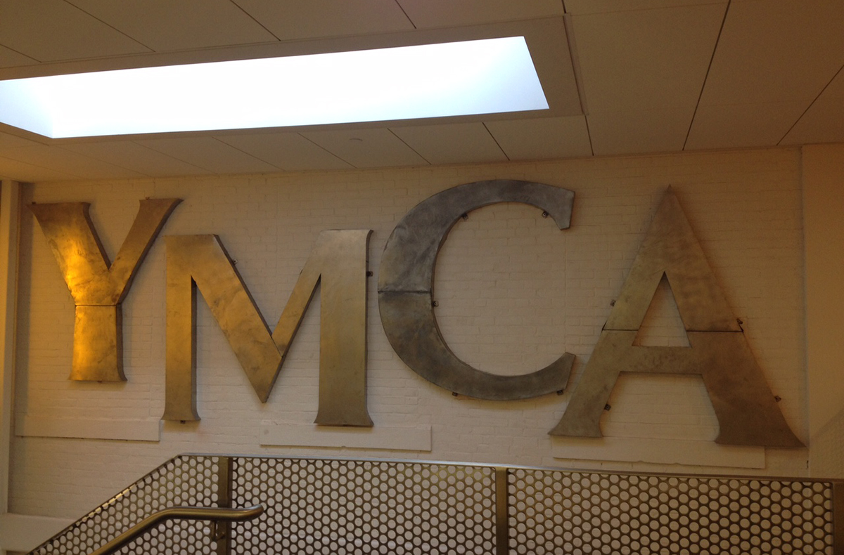 The original hand-hammered YMCA letters that were affixed to the outside of the building were repurposed as art, and are now used inside the building. Photo by Melissa Malamut