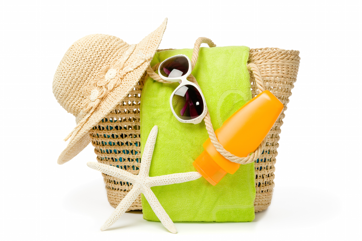 Beach bag with items for a day at the seaside on white background via Shutterstock