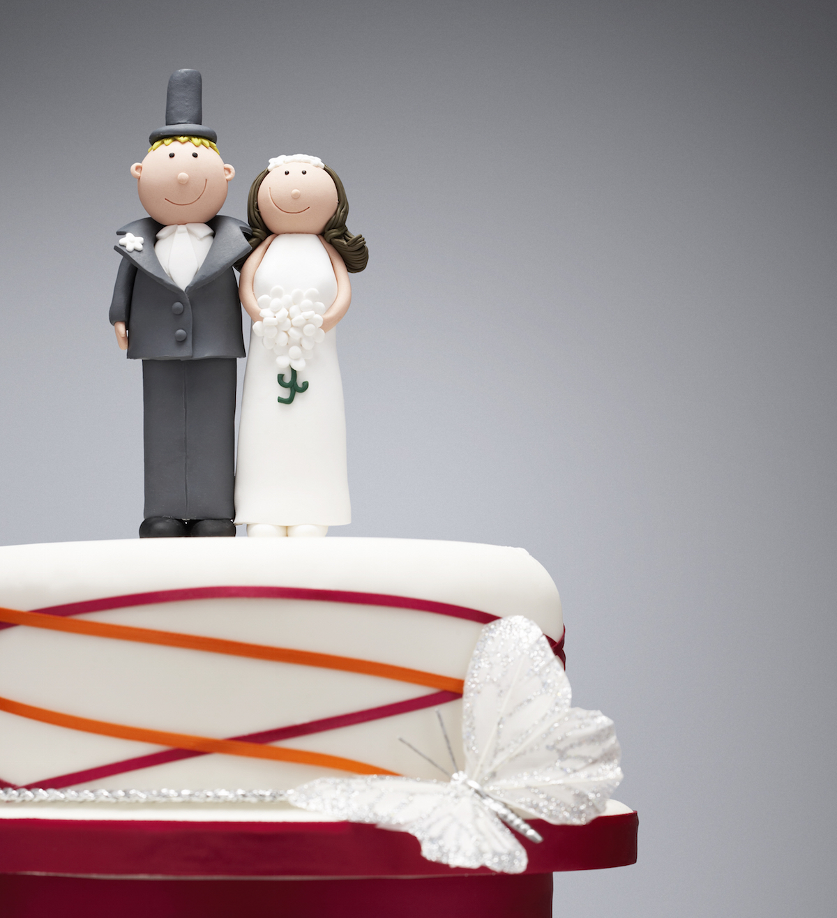Comical Bride And Groom Figurines On Top Of Wedding Cake Via Shutterstock