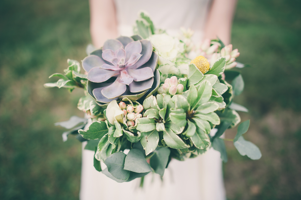 Bride holding wedding bouquet of succulents via Shutterstock