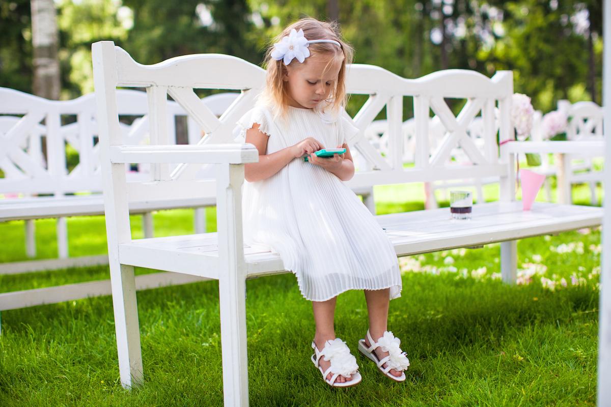 Adorable little girl at wedding ceremony via Shutterstock