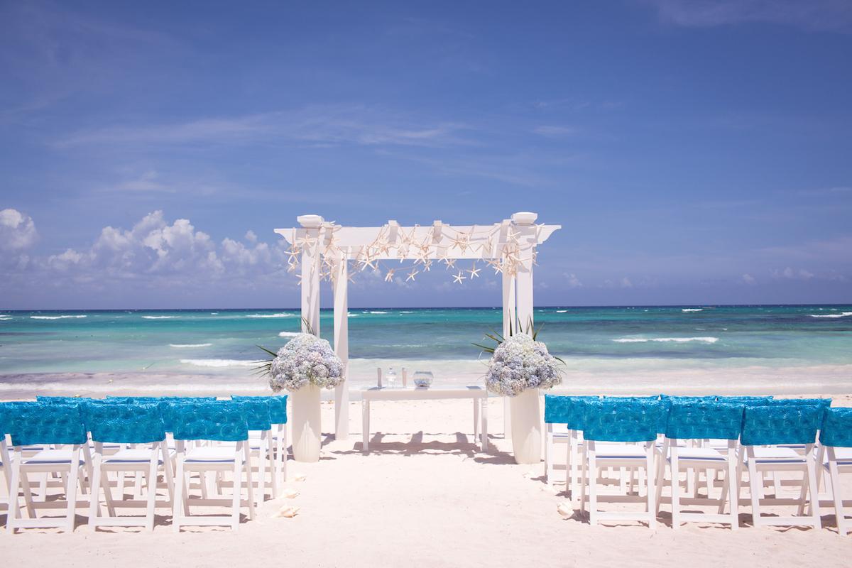 Beach wedding ceremony with blue water via Shutterstock
