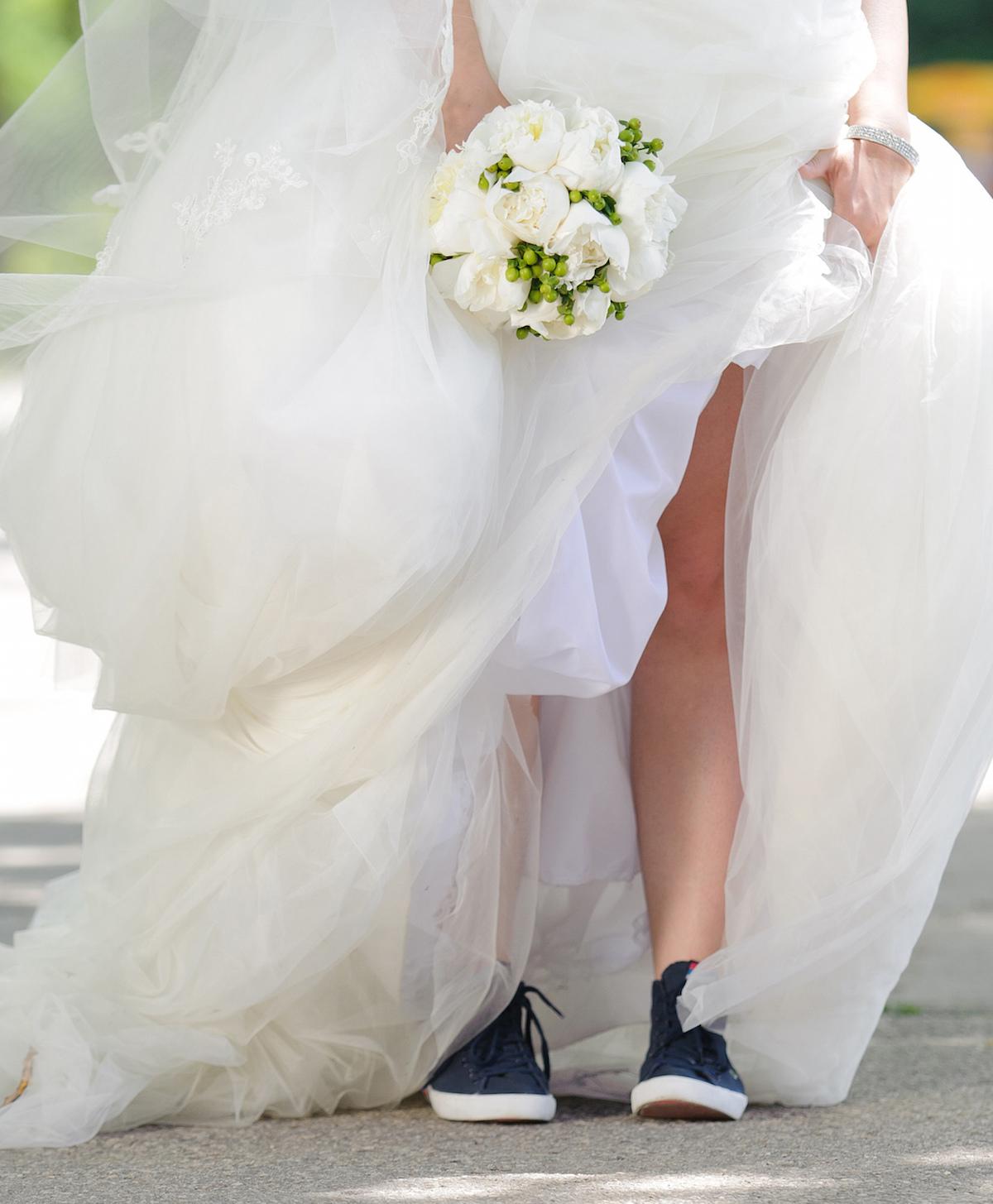 Bride in sneakers in park via Shutterstock