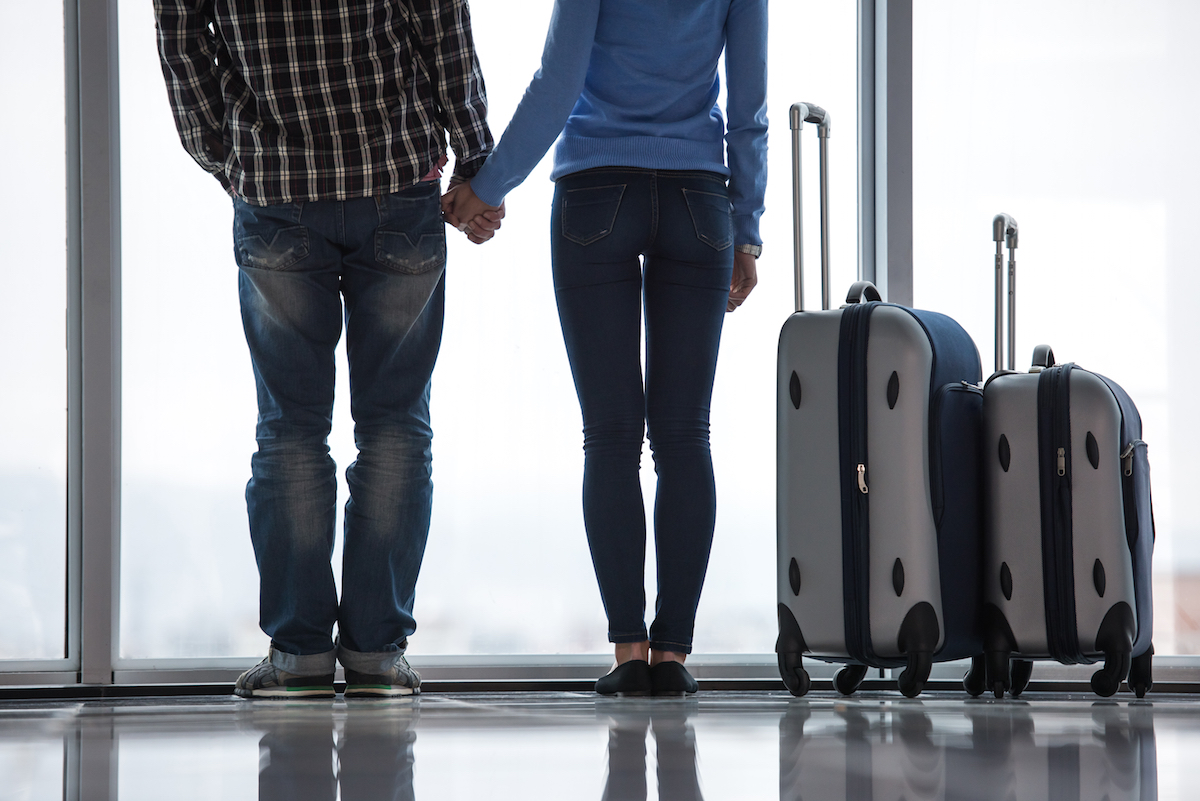 Young couple with suitcases are looking through airport window while waiting for flight. Back view. Via Shutterstock