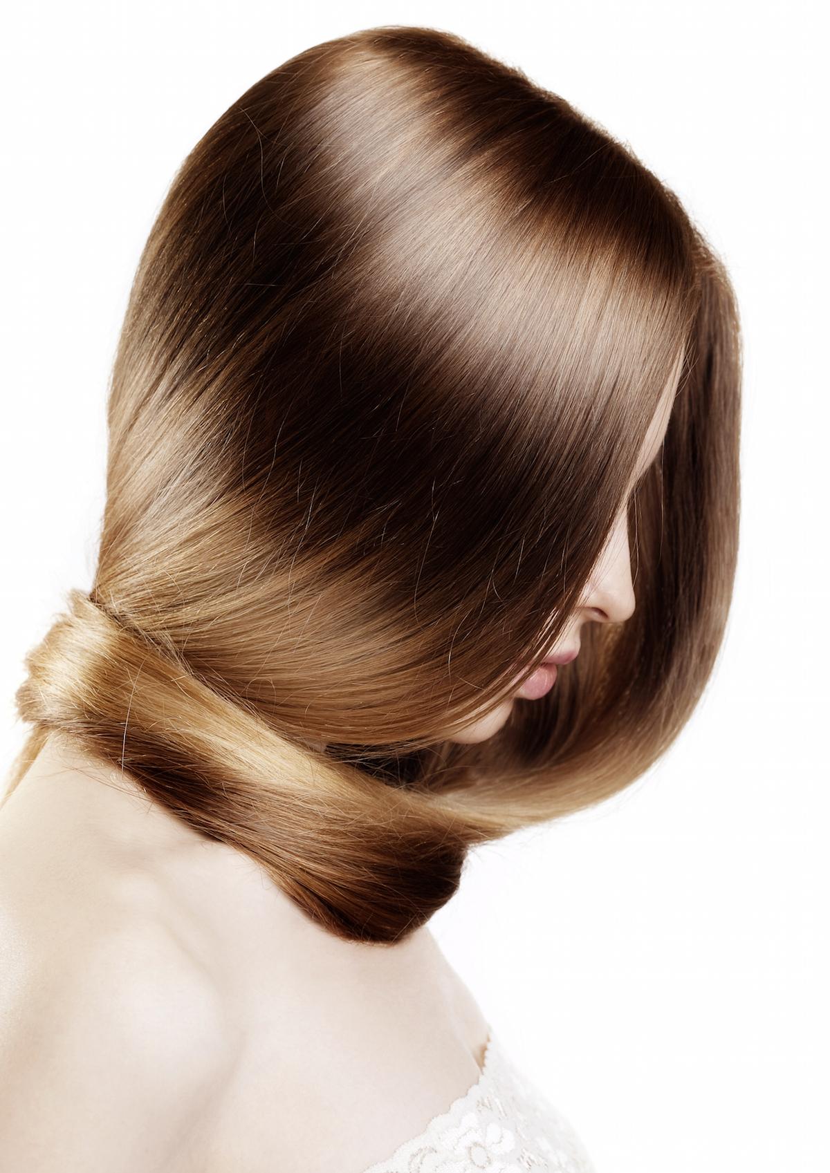 Young beautiful woman with luxurious hair via Shutterstock