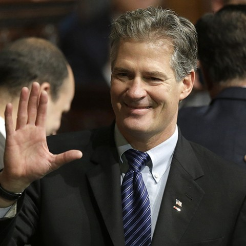 Former U.S. Sen. Scott Brown, center, greets people on the floor of the House Chamber at the Statehouse, in Boston, Thursday, Jan. 8, 2015, before inaugural ceremonies for Charlie Baker. Baker was sworn in as governor during a ceremony in the House Chamber before members of the state Supreme Judicial Court, House and Senate lawmakers, and other top elected officials. (AP Photo/Steven Senne)