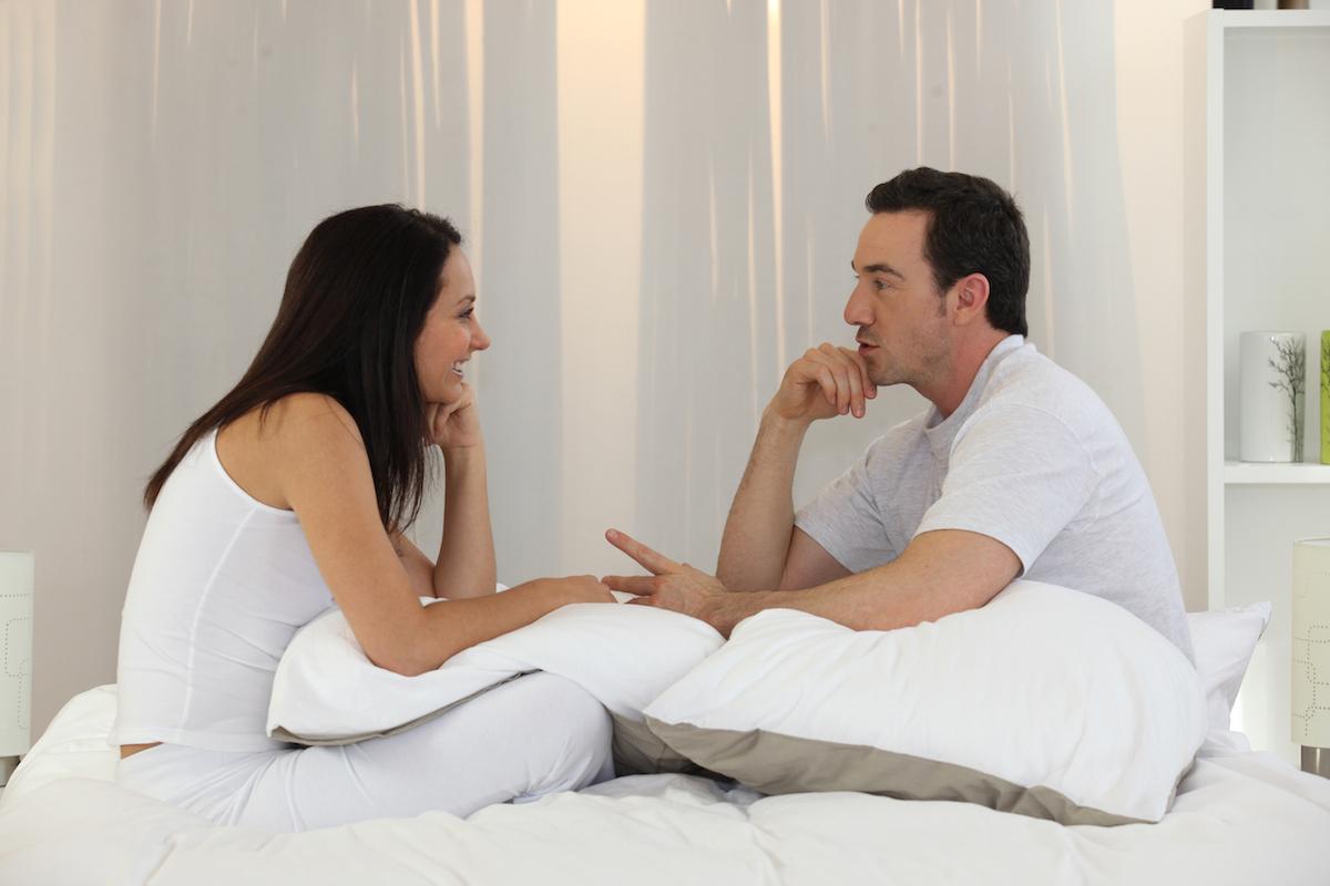 Couple talking in bedroom via Shutterstock
