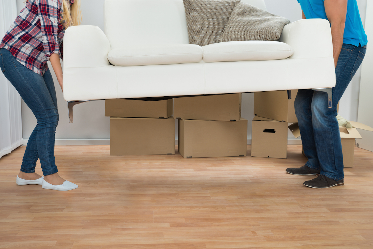 Happy young couple carrying couch in new home via Shutterstock