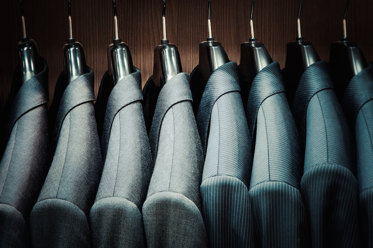 Row of mens suit jacket on hangers via Shutterstock