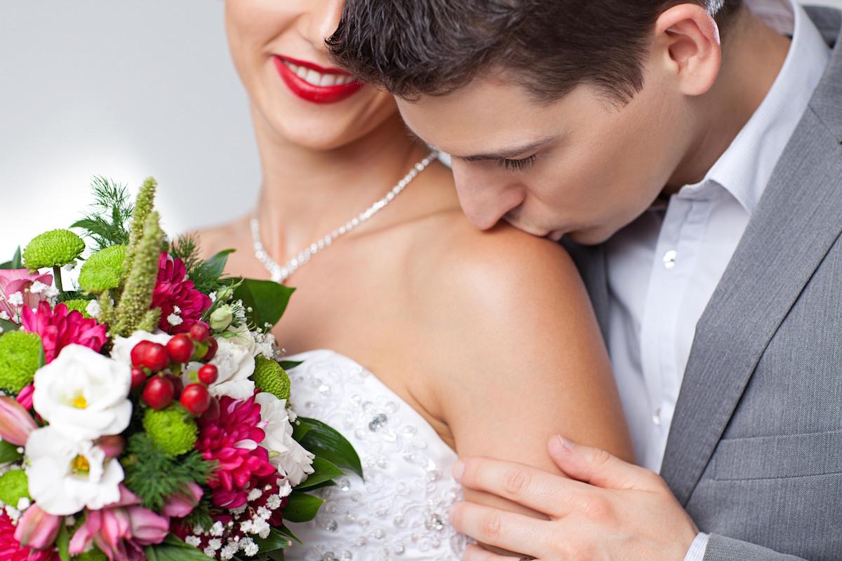Close up of groom kissing brides shoulder via Shutterstock