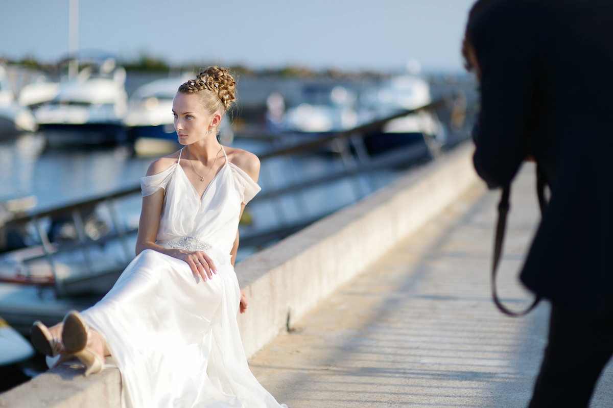 Bride posing while her groom is shooting with an old camera via Shutterstock