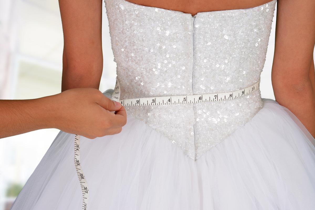Woman in wedding dress getting measured via Shutterstock