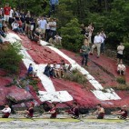 People watch from a painted rock on shore as Harvard leads Yale on the four-mile course along the Thames River for the 146th Harvard-Yale Regatta in New London, Conn., Saturday, May 28, 2011. Harvard defeated Yale for 11th time in 12 years in nation's oldest intercollegiate sporting event. (AP Photo/Jessica Hill)