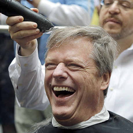 Massachusetts Gov. Charlie Baker reacts as he gets a buzz cut during a fundraising drive at Granite Telecommunications in Quincy, Mass., Tuesday, April 7, 2015, in support of the Dana-Farber Cancer Institute. Baker joined more than 500 company employees who shaved their heads to raise more than $3.5 million for cancer research. (AP Photo/Elise Amendola)