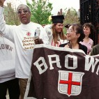 Entertainer Bill Cosby waves to the crowd Monday, May 29, 2000, in Providence, R.I., as he attends the Brown University graduation, returning for the 15th reunion of the class of 1985, of which he was an honorary graduate. Cosby helps carry the class banner with  Sandra Loh, center, and Sirat Golden, right.  (AP Photo/Michael Dwyer)