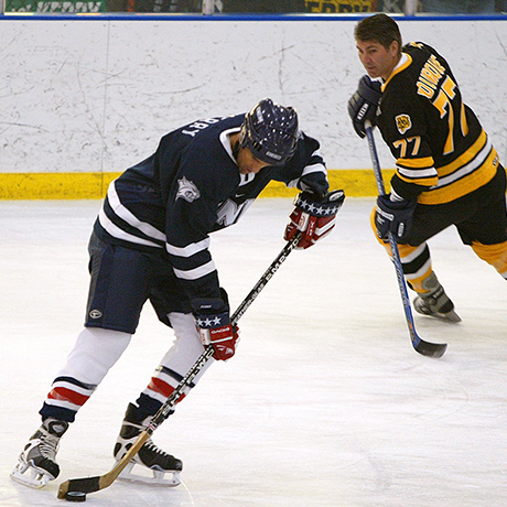 Democratic presidential hopeful Sen, John Kerry, D-MA,, handles the puck as teammate and Boston Bruins retired star Ray Bourque (77) circles around him during a campaign stop Saturday afternoon  Jan. 24, 2004 in Manchester, N.H. At the event Kerry played hockey with former players of the NHL's Boston Bruins, members of the U.S. Women's National team, firefighters and New Hampshire high school players  (AP Photo/Stephan Savoia)