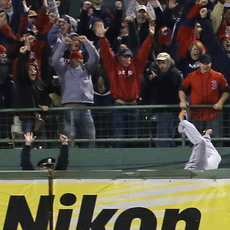 Boston Police officer Steve Horgan celebrates as Detroit Tigers' Torii Hunter falls over the right field fence into the bullpen trying to catch a grand slam hit by Boston Red Sox' David Ortiz during Game 2 of the American League baseball championship series Sunday, Oct. 13, 2013, in Boston. (AP Photo/Matt Slocum)
