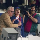 "RETRANSMISSION TO CORRECT SPELLING OF NAME - FILE - In this April 4, 1994, file photo, first lady Hillary Rodham Clinton, right, and Chicago Cubs announcer Harry Caray, left, sing ""Take Me Out To The Ball Game"" during the seventh inning stretch at Wrigley Field in Chicago. The Cubs are leaving WGN Radio that's been their radio home for 90 years. Radio president Jimmy de Castro confirmed on the air Wednesday, June 4, 2014, media reports that the Cubs are leaving the station after this season. (AP Photo/John Zich, File)"