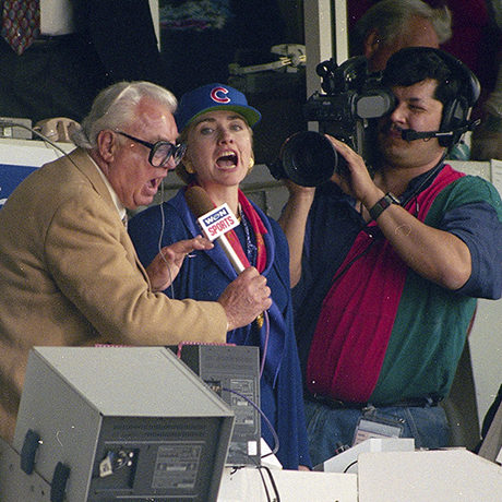 """RETRANSMISSION TO CORRECT SPELLING OF NAME - FILE - In this April 4, 1994, file photo, first lady Hillary Rodham Clinton, right, and Chicago Cubs announcer Harry Caray, left, sing """"Take Me Out To The Ball Game"""" during the seventh inning stretch at Wrigley Field in Chicago. The Cubs are leaving WGN Radio that's been their radio home for 90 years. Radio president Jimmy de Castro confirmed on the air Wednesday, June 4, 2014, media reports that the Cubs are leaving the station after this season. (AP Photo/John Zich, File)"""