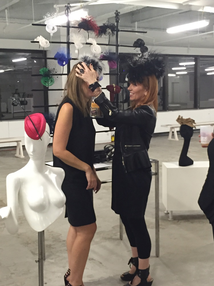 Milliner Marie Galvin helps a customer adjust a whimsical head-piece.
