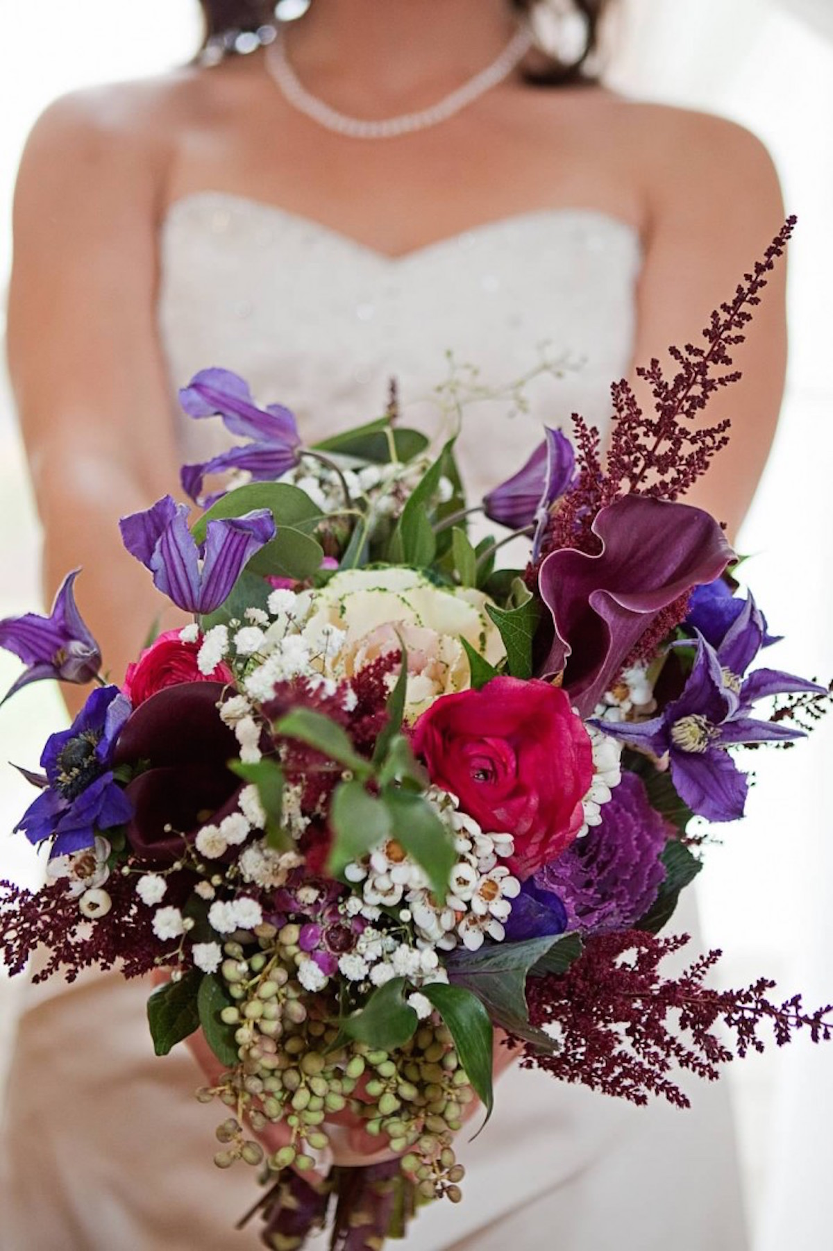 mini kale accented by ranunculus, waxflower, astilbe, calla lilies and purple clematis/Courtesy photo