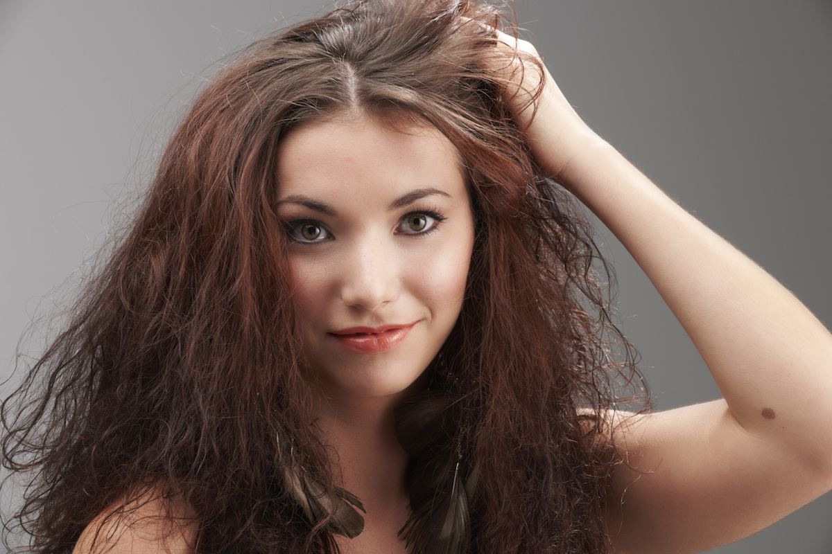 woman grabbing her tangled hair in frustration on grey background via Shutterstock