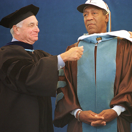 Comedian Bill Cosby recieves a cowl from Tufts University Trustees Nate Gantcher, left, and Marilyn Ducksworth during Tuft University's 144th commencement Sunday, May 21, 2000 in Medford, Mass. Cosby, who recieved an honorary Doctor of Arts Degree from the University, also delivered the commencement address.  (AP Photo/Patricia McDonnell)