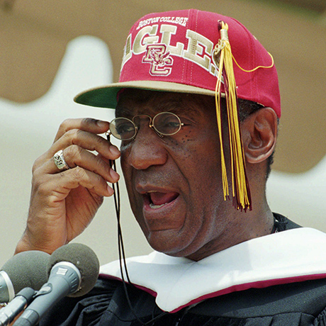 With a Boston College baseball cap replacing his mortarboard, Entertainer Bill Cosby adjusts his reading glasses while delivering his commencement address at Boston College in Chestnut Hill, Mass., Monday May 20, 1996.  (AP Photo/Charles Krupa)
