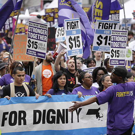 Protesters, including college students, fast-food restaurant employees and other workers, display placards as they march Tuesday, April 14, 2015, in Boston. Organizers of the event are calling for the nation's lowest paid workers to earn at least $15 per hour. (AP Photo/Steven Senne)